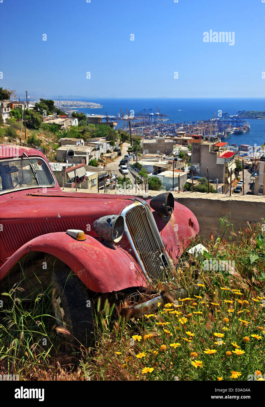 Abandoned old car at Perama, Piraeus, Attica, Greece. In the background you can see the containers' terminal. - Stock Image
