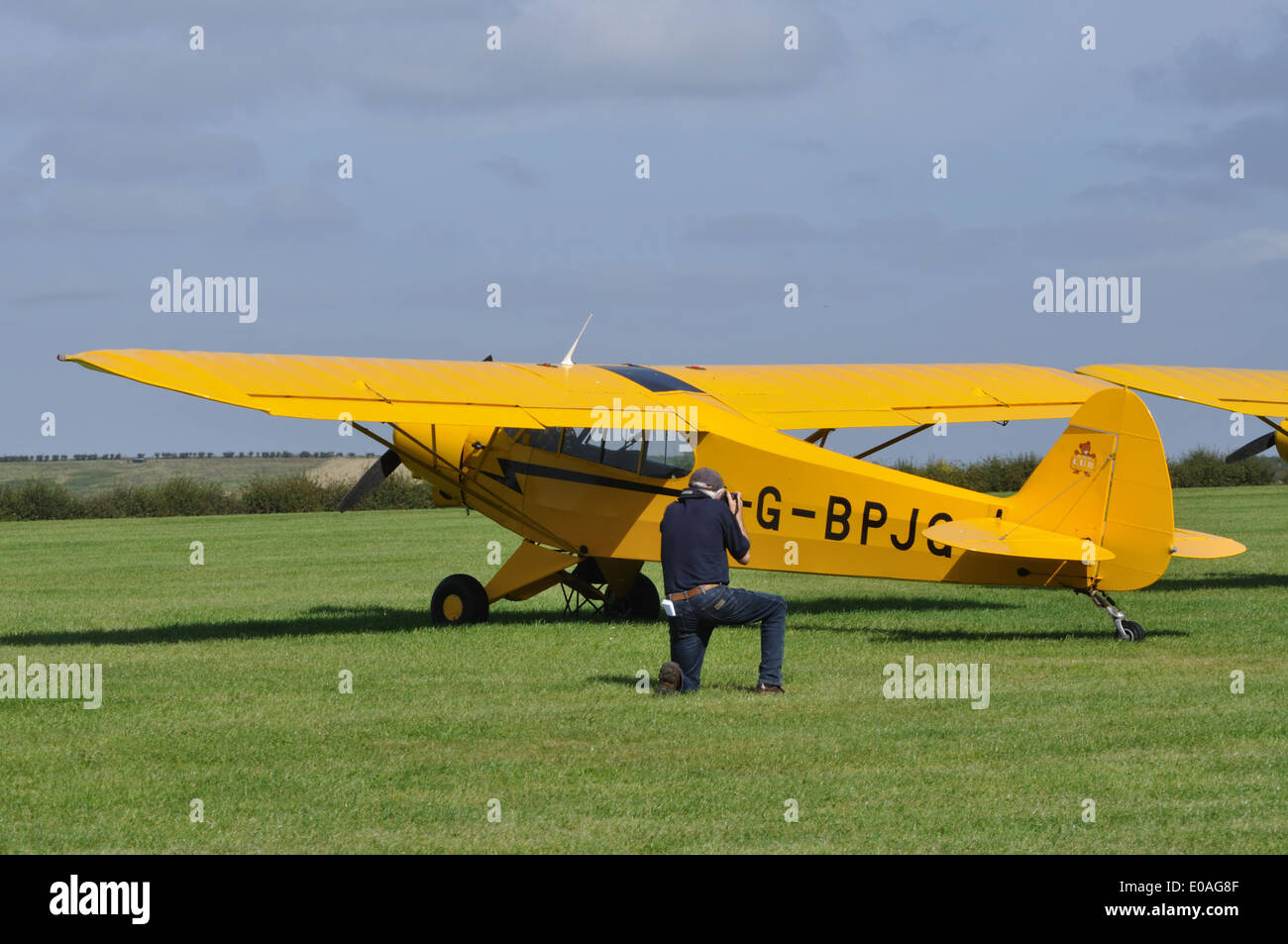 Aircraft enthusiast photographing 1965 Piper PA-18-150 Super Cub G-BPJG at Compton Abbas Airfield, Dorset. - Stock Image