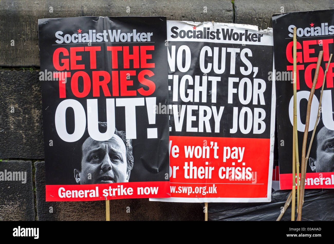 Socialist Worker placards depicting David Cameron lean against a wall prior to the May Day Rally in Edinburgh, Scotland, UK. - Stock Image