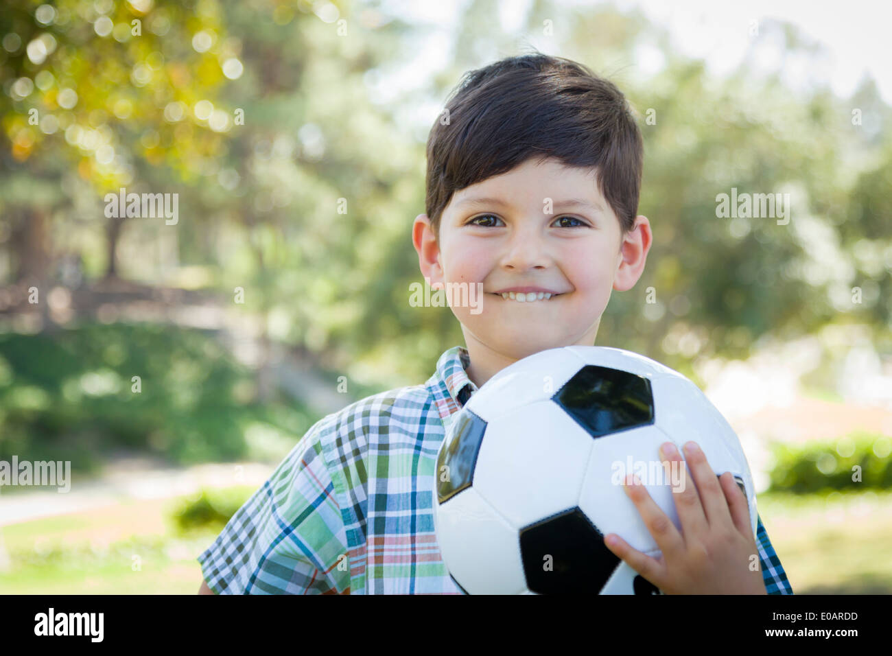Cute Young Boy Playing with Soccer Ball Outdoors in the Park. - Stock Image