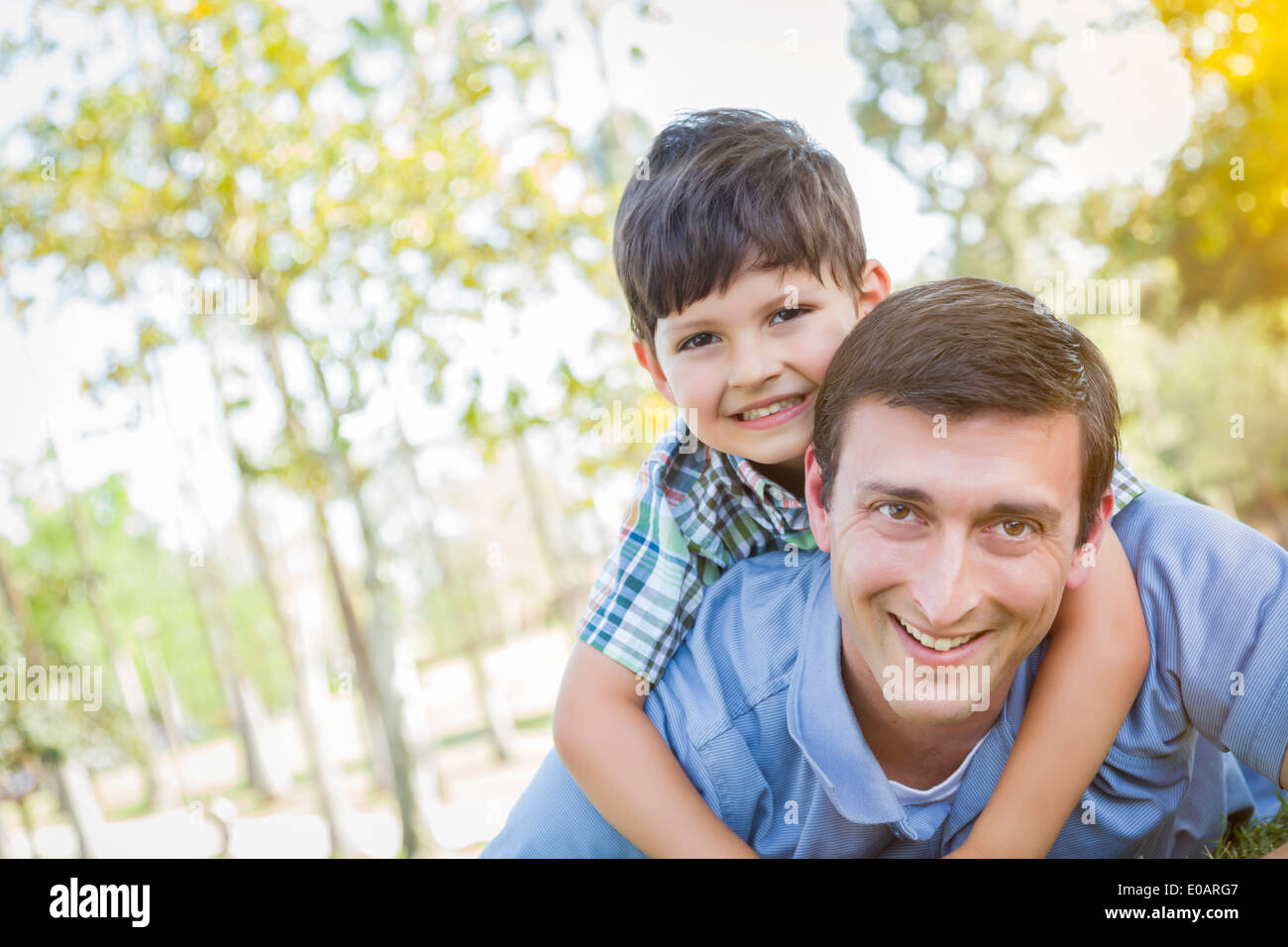 Mixed Race Father and Son Playing Together in the Park. - Stock Image