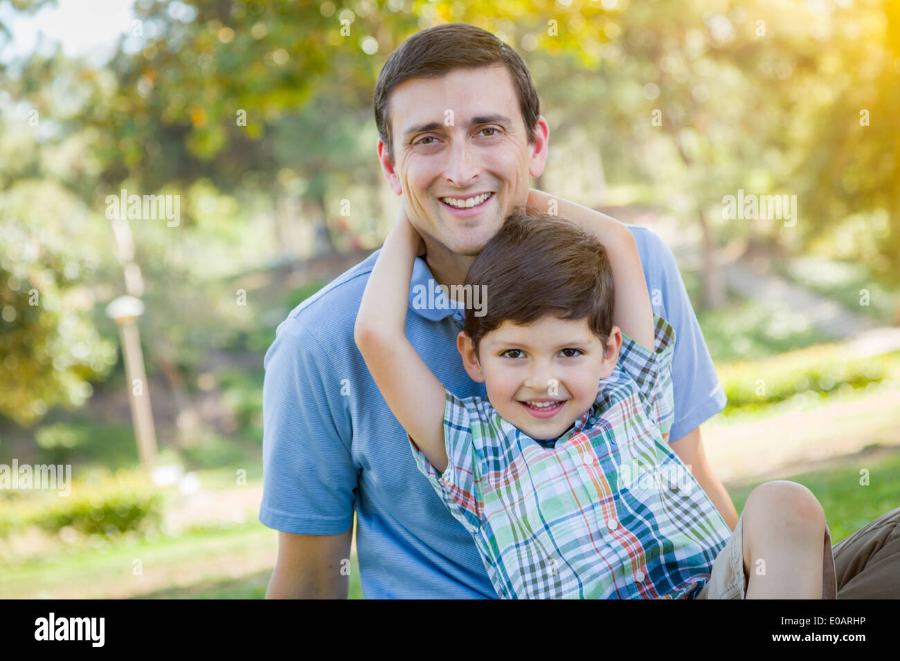 Handsome Mixed Race Father and Young Son Portrait in the Park. - Stock Image