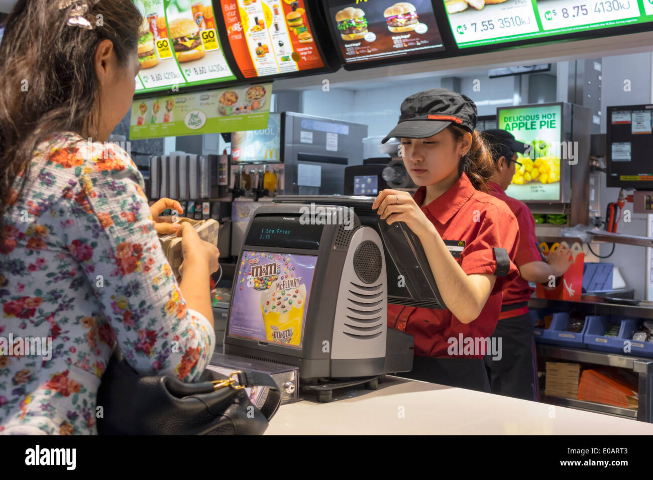 Sydney Australia NSW New South Wales CBD Central Business District Circular Quay McDonald's restaurant fast food counter ordering Asian woman job empl - Stock Image