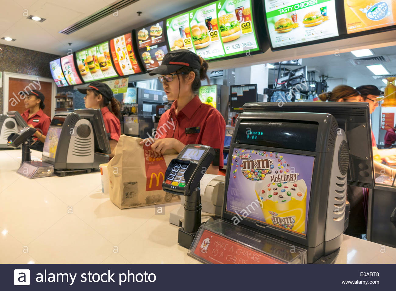 Sydney Australia NSW New South Wales CBD Central Business District Circular Quay McDonald's restaurant fast food counter Asian woman job uniform emplo - Stock Image
