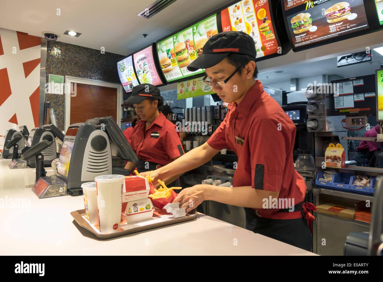 Sydney Australia NSW New South Wales CBD Central Business District Circular Quay McDonald's restaurant fast food counter ordering Asian man job employ - Stock Image