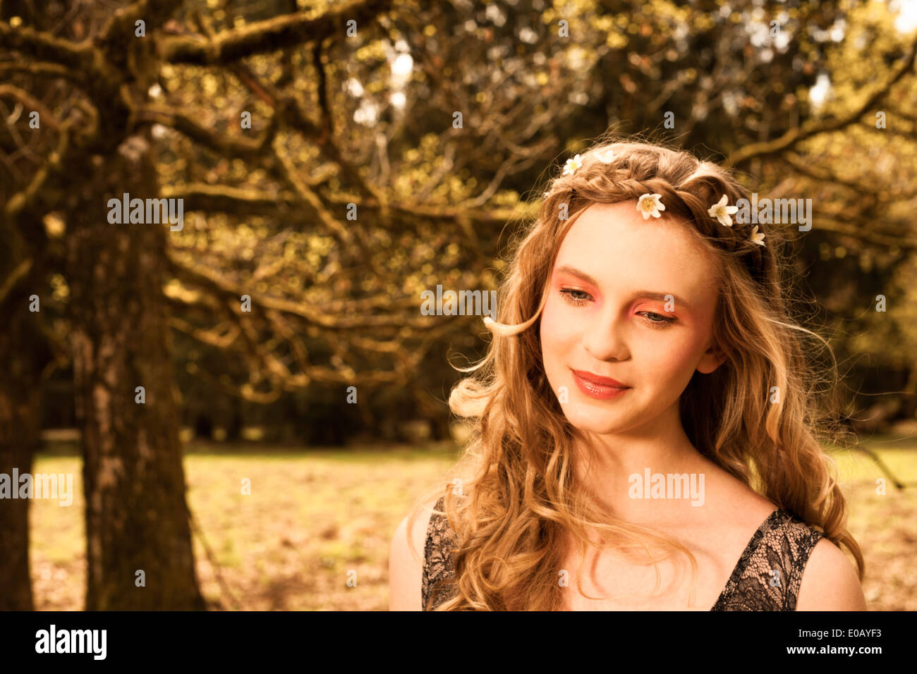 Portrait of daydreaming young woman with flowers in hair - Stock Image