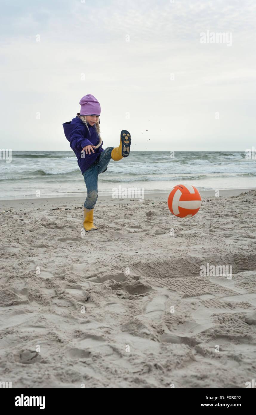 Denmark, Jutland, Vejers Strand, girl kicking ball on beach - Stock Image