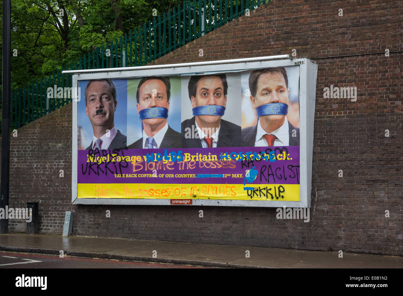 Tottenham, London UK. 8th May 2014. A billboard showing an advertisement for political party UKIP is defaced with the word 'Racist' in Tottenham, London. Tottenham is a London neighbourhood that is recognised for its racial diversity.  Credit:  Patricia Phillips/Alamy Live News - Stock Image