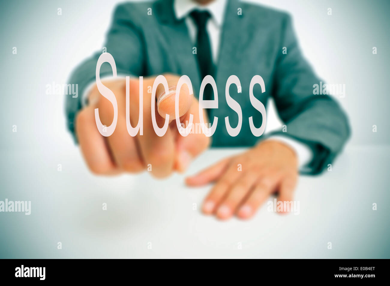 businessman sitting in a desk pointing the finger to the word success written in the foreground - Stock Image