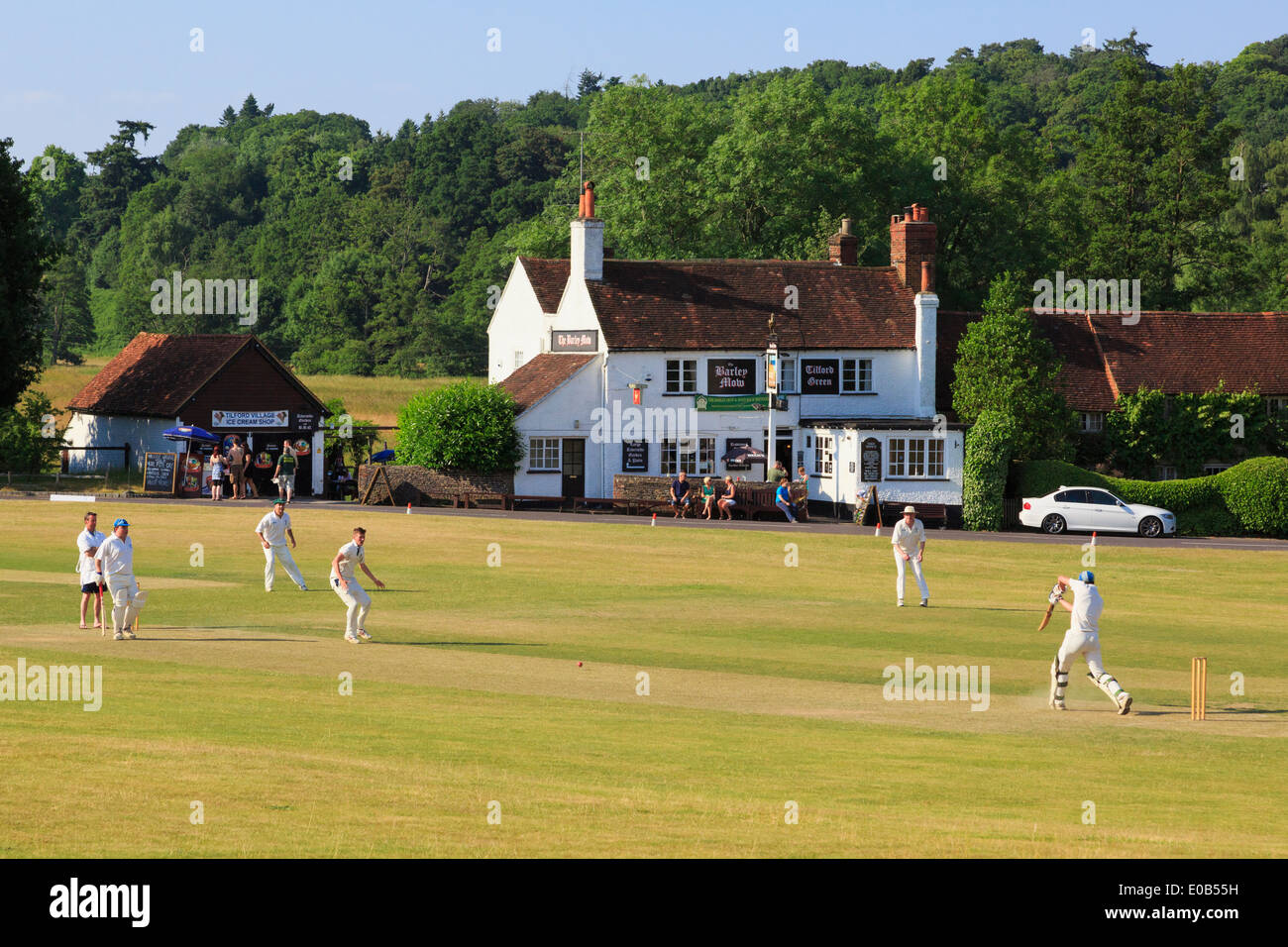 Local teams playing a cricket match on a village green in front of Barley Mow pub on a summer's evening. Tilford Stock Photo