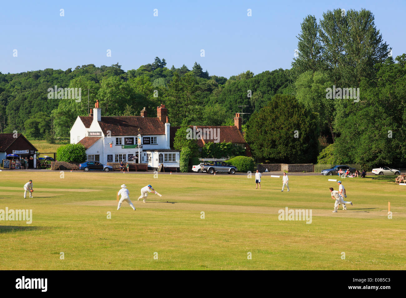Local teams playing a cricket match on village green in front of Barley Mow pub on a summer's evening. Tilford Surrey Stock Photo