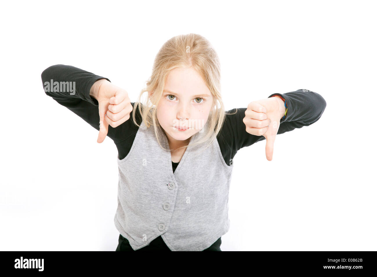 young girl in studio with both thumbs down against white background - Stock Image