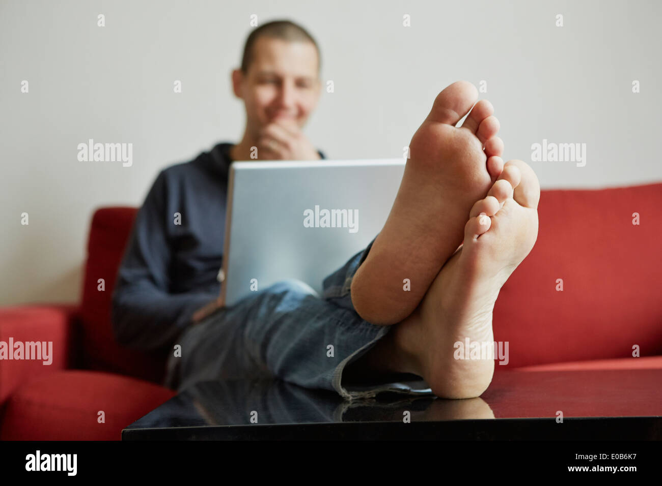 Mid adult man relaxing on sofa engrossed in laptop - Stock Image