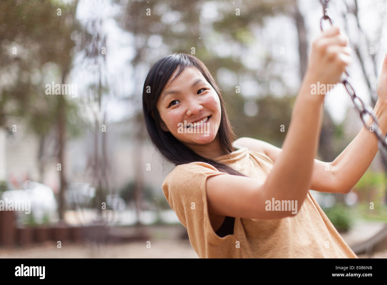 Mid adult woman swinging in city park - Stock Image