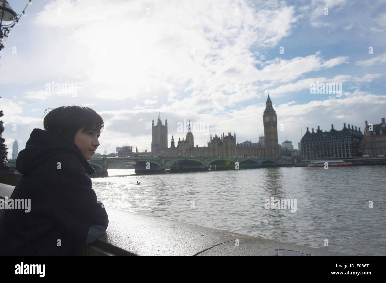 Boy by River Thames, Palace of Westminster in background, London - Stock Image