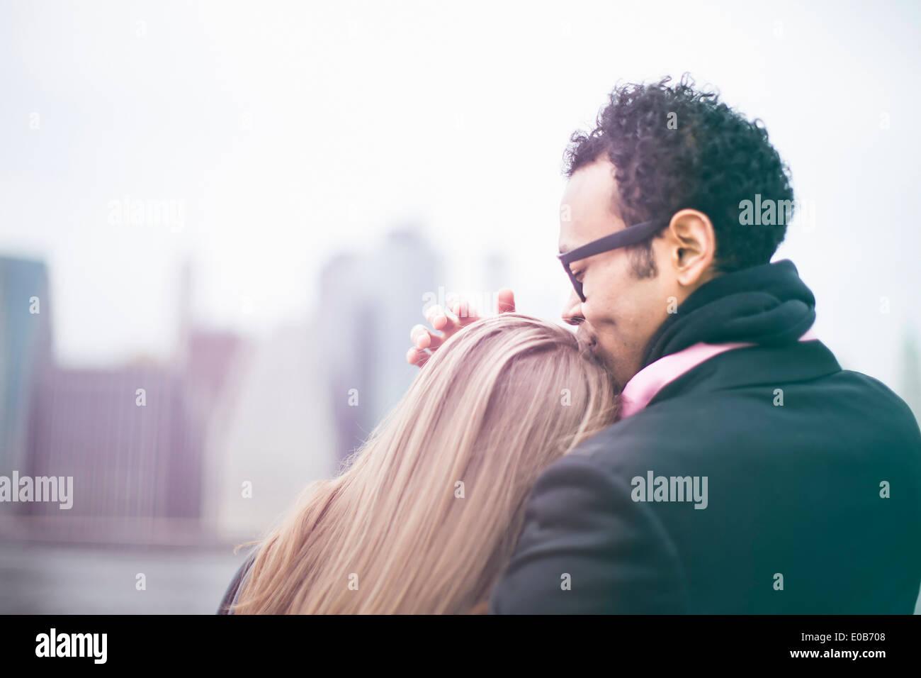 Affectionate young couple and Manhattan skyline, New York, USA - Stock Image