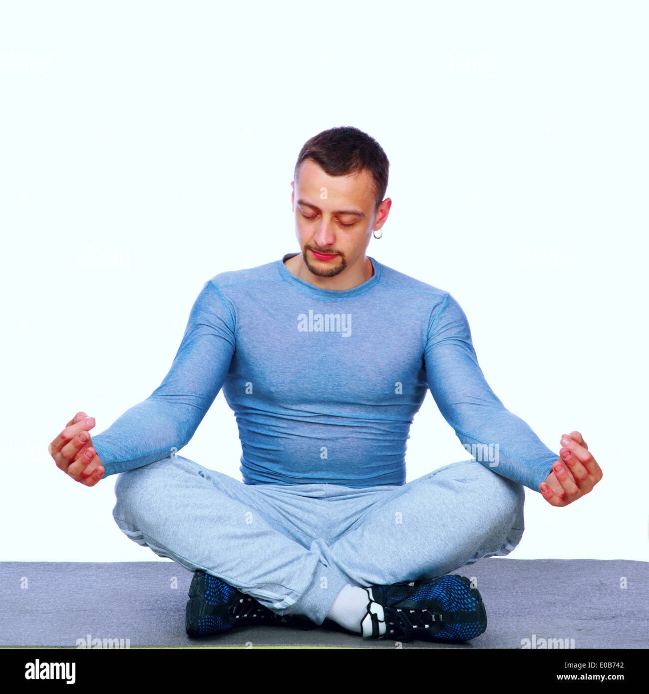 Concentrated sportsman sitting in the lotus position on gray background - Stock Image