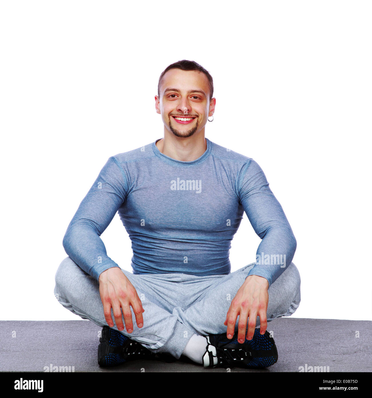 Happy sportsman sitting in the lotus position over white background - Stock Image