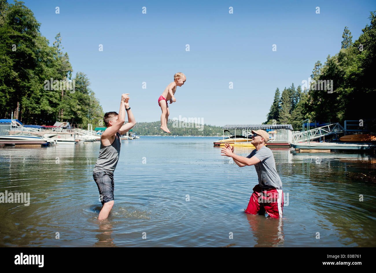 Female toddler thrown and caught mid air by young men - Stock Image