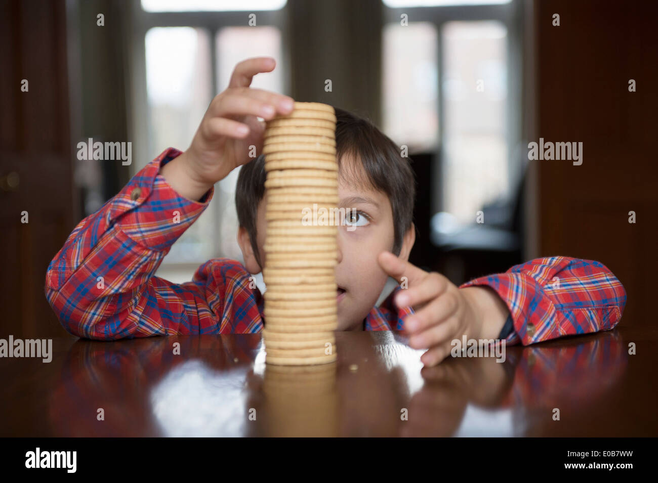 Boy stacking up biscuits - Stock Image