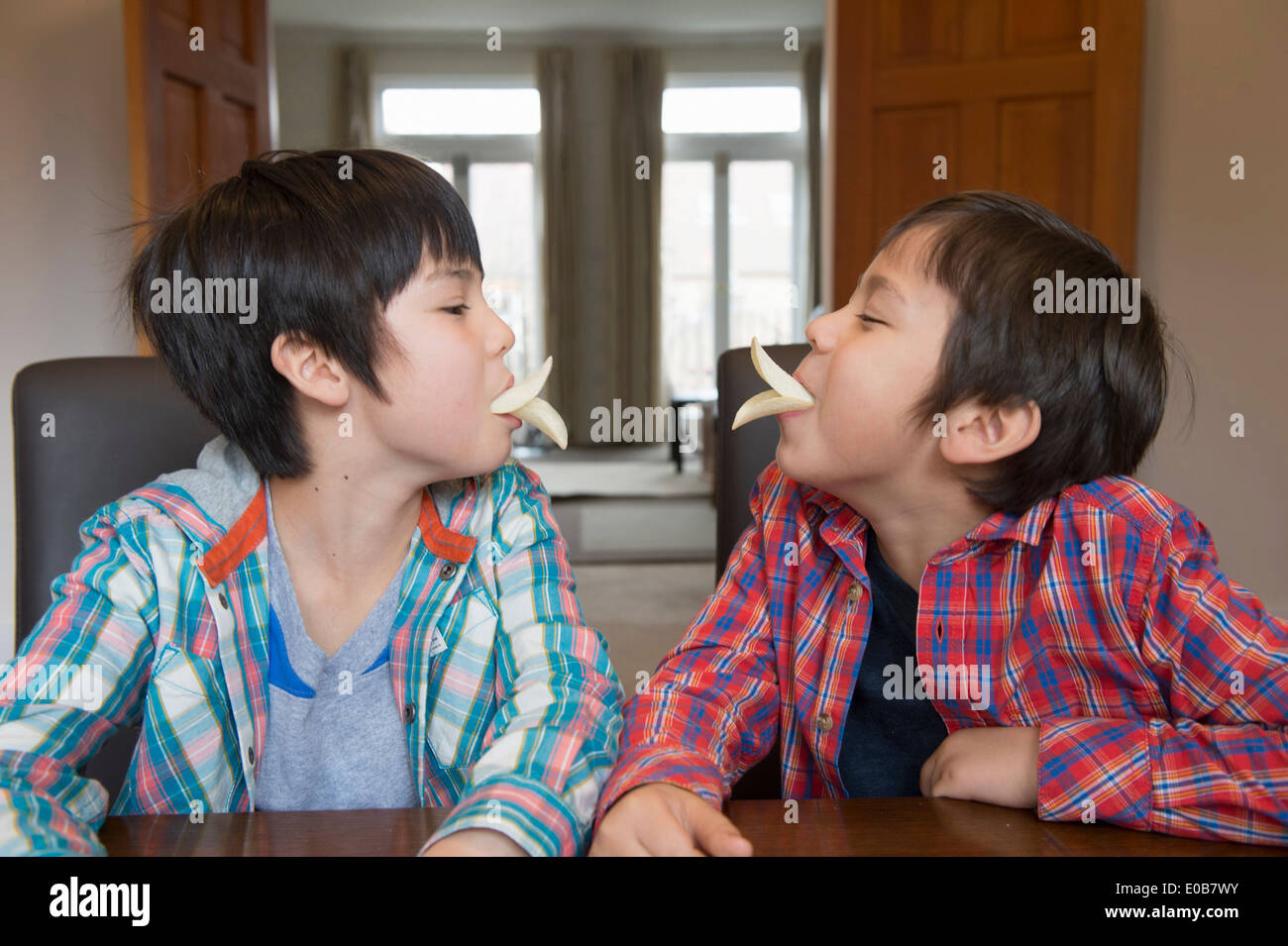 Brothers imitating bird beak with crisps - Stock Image