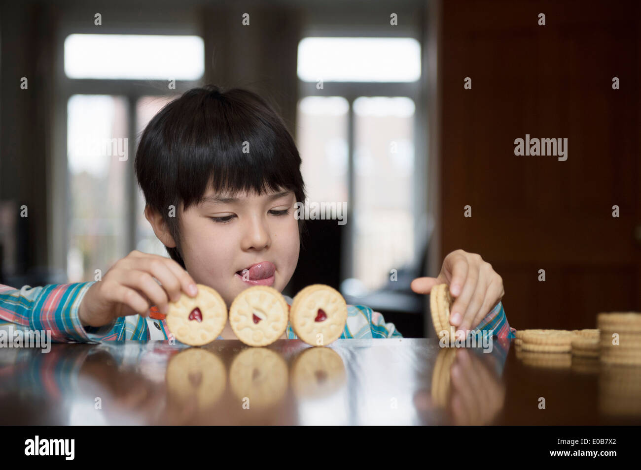 Boy playing with biscuits - Stock Image