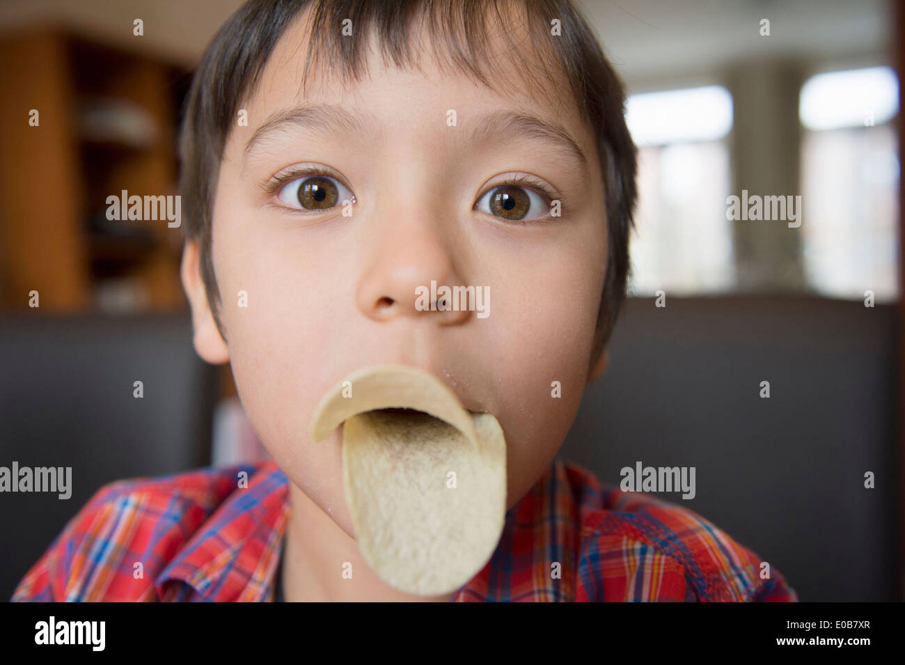Boy imitating bird beak with crisps - Stock Image