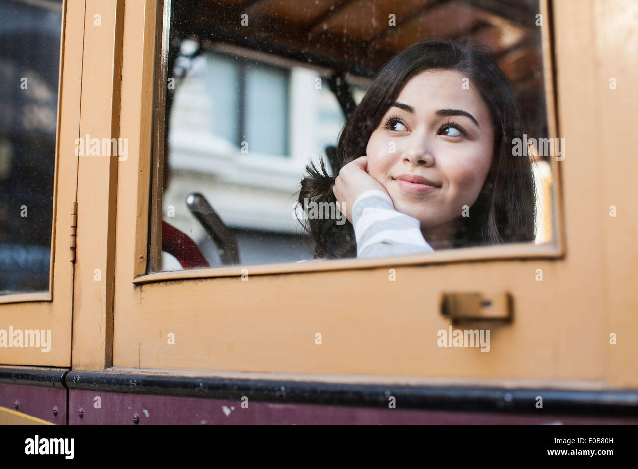 Portrait of young woman, looking through window of cable car - Stock Image