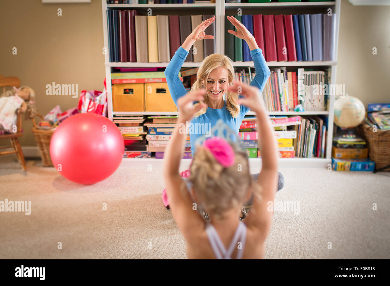 Mother and young daughter practicing ballet in sitting room - Stock Image