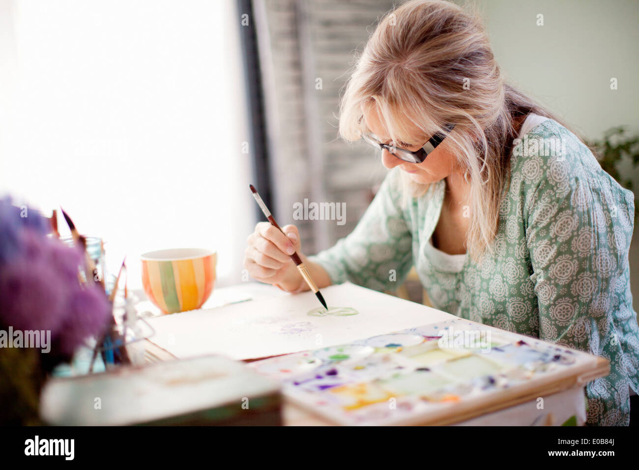 Mature female artist watercolour painting in studio - Stock Image
