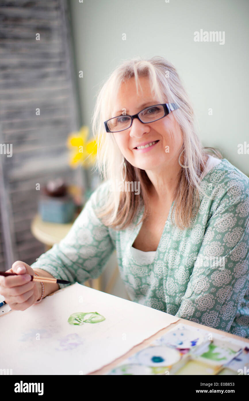 Portrait of mature female artist watercolour painting in studio - Stock Image