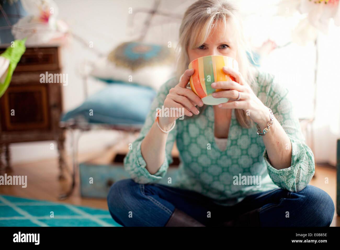 Mature woman sitting cross legged drinking coffee - Stock Image