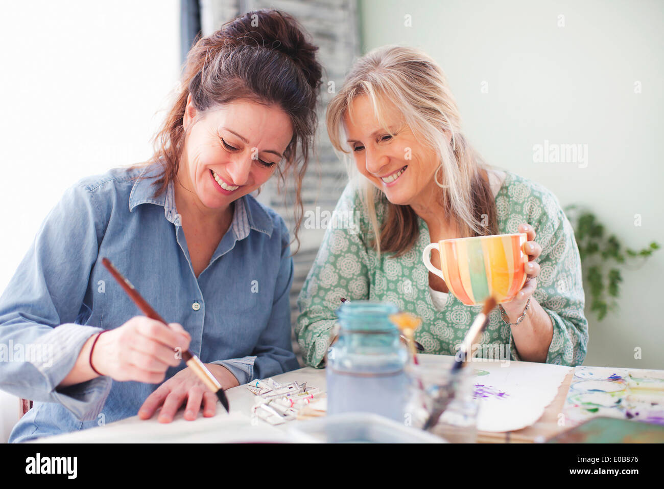 Two mature female artists painting in studio - Stock Image