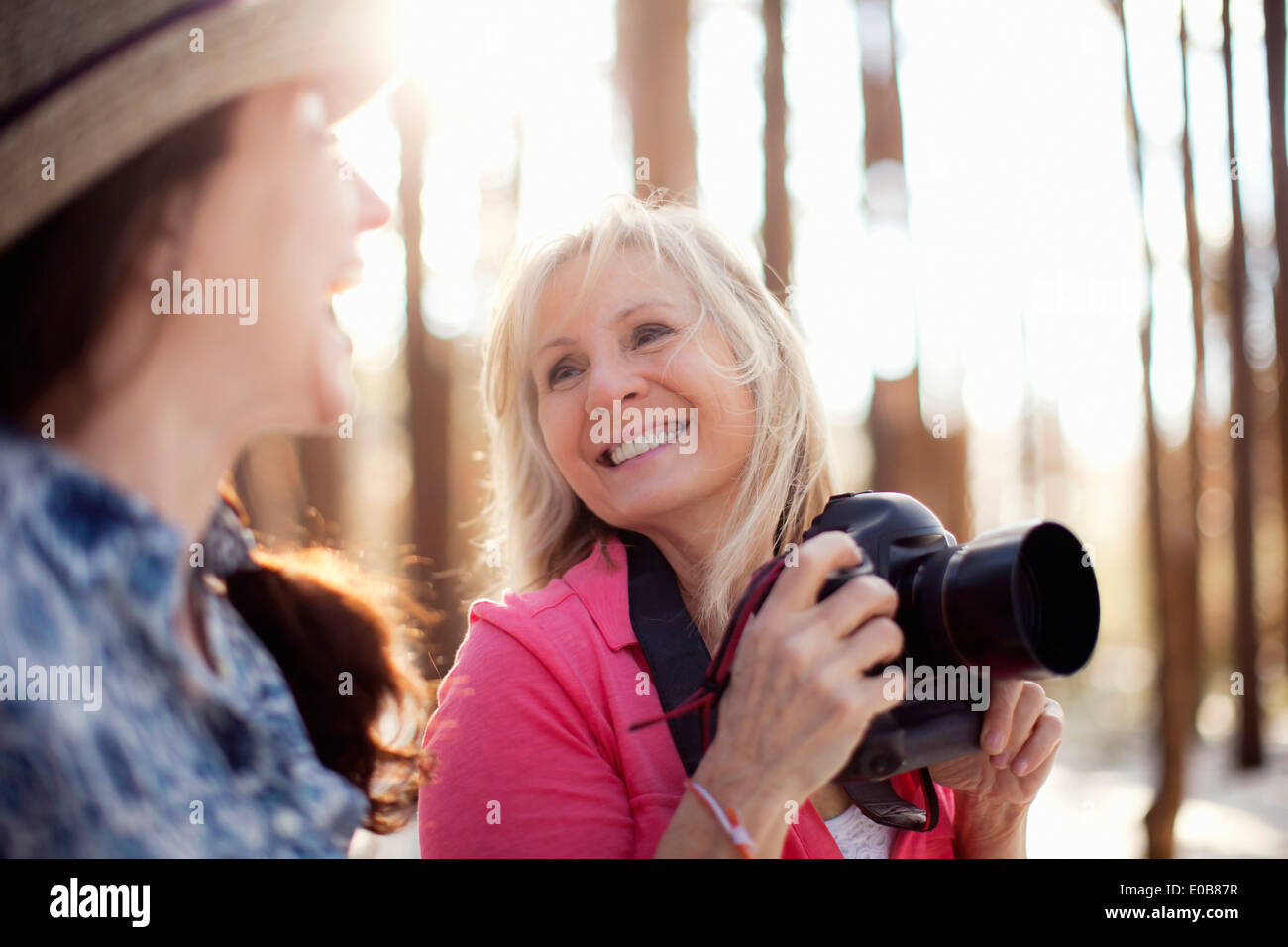 Two mature women with digital camera in forest - Stock Image