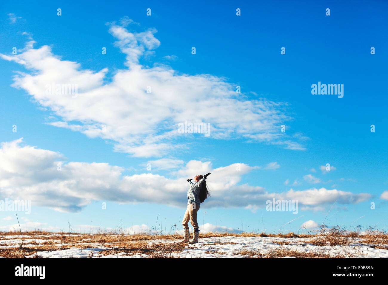 Mature woman with arms outstretched in landscape - Stock Image