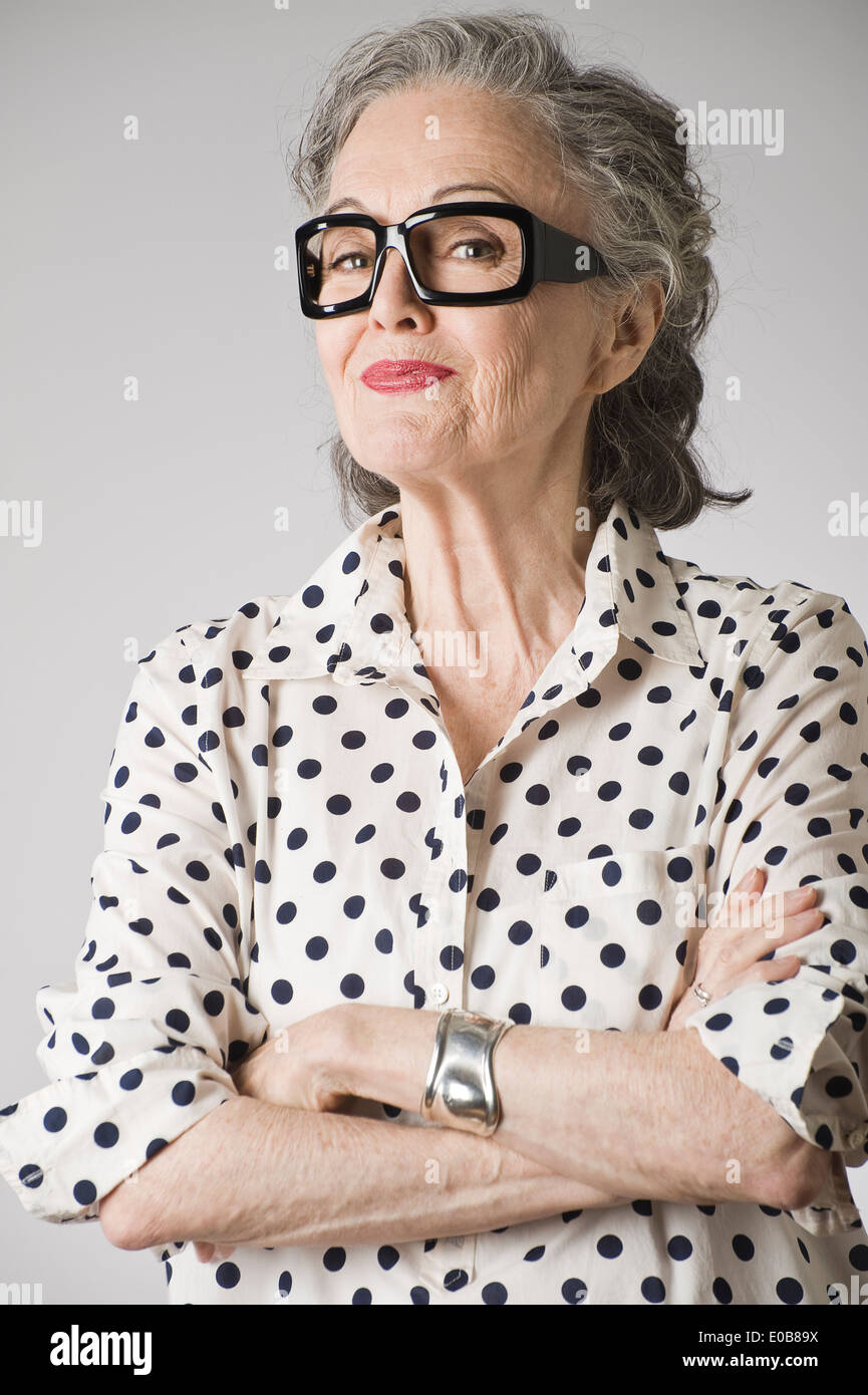 Portrait of senior woman, arms crossed - Stock Image