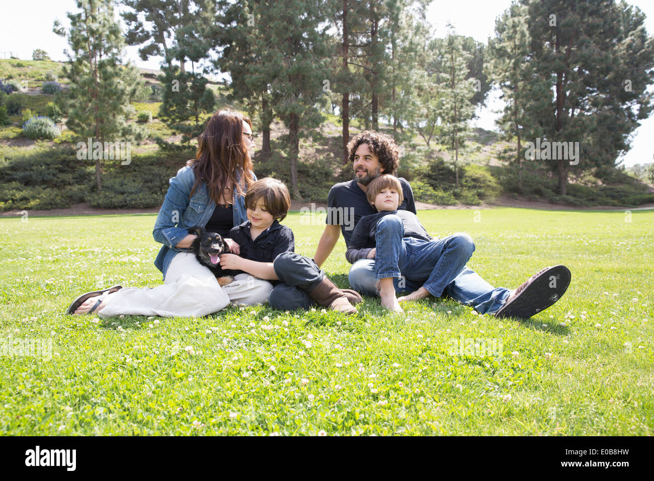 Family with two boys and dog sitting in park - Stock Image
