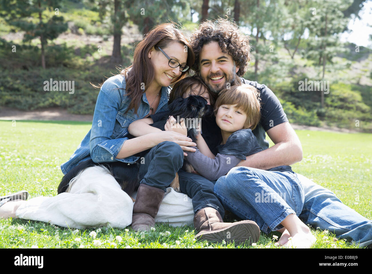 Portrait of family with two boys and dog sitting in park - Stock Image