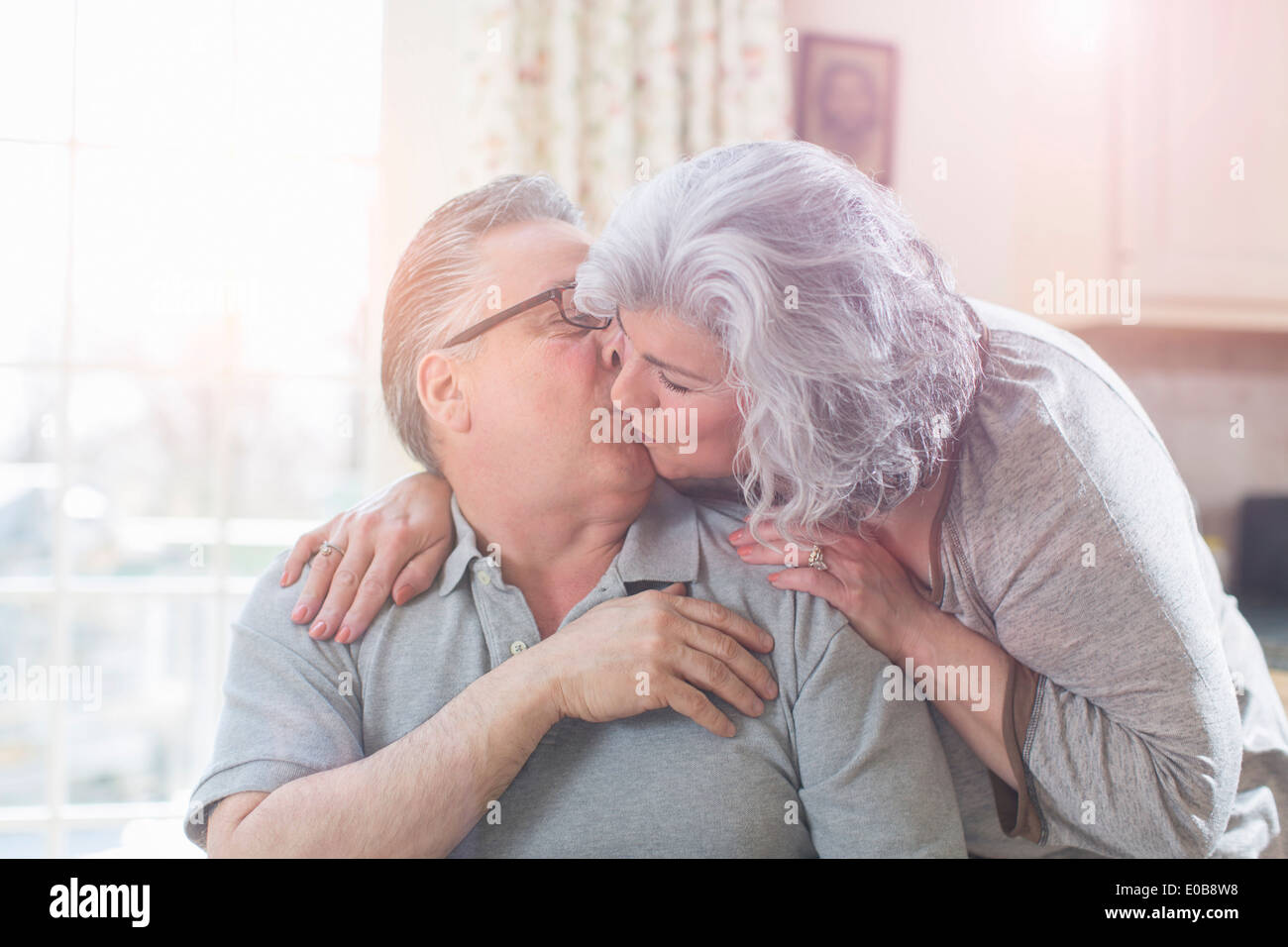 Affectionate mature adult couple kissing at home - Stock Image