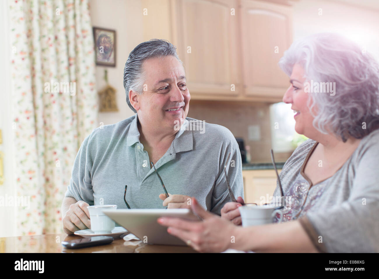 Mature adult couple having breakfast at home - Stock Image