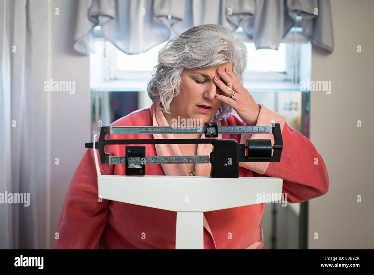 Unhappy mature woman on bathroom weighing scales - Stock Image