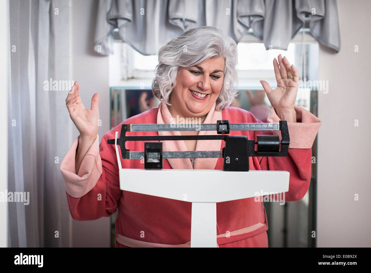 Happy mature woman on bathroom weighing scales - Stock Image