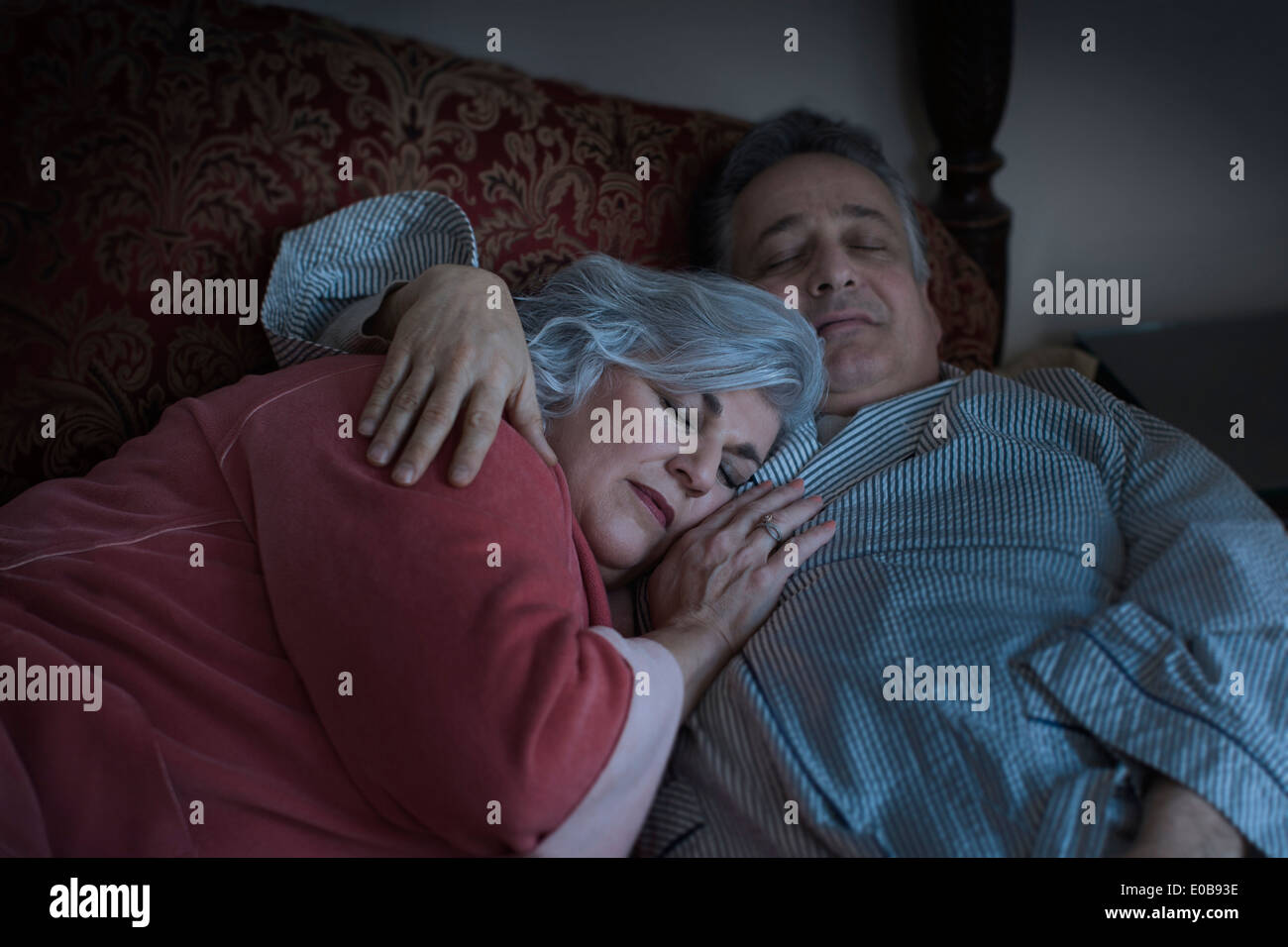 Affectionate mature adult couple sleeping on bed - Stock Image