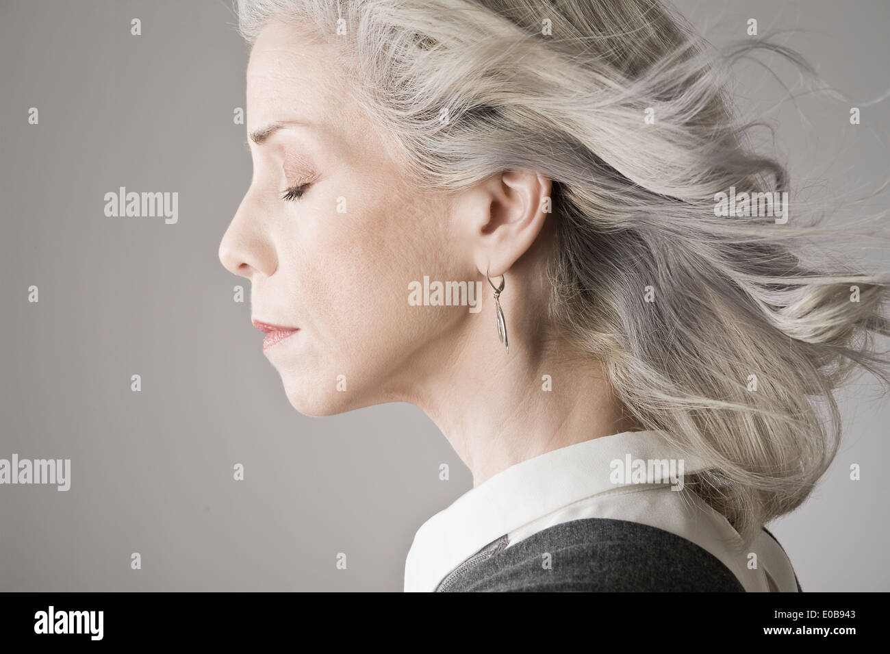 Side view of mature woman with eyes closed - Stock Image