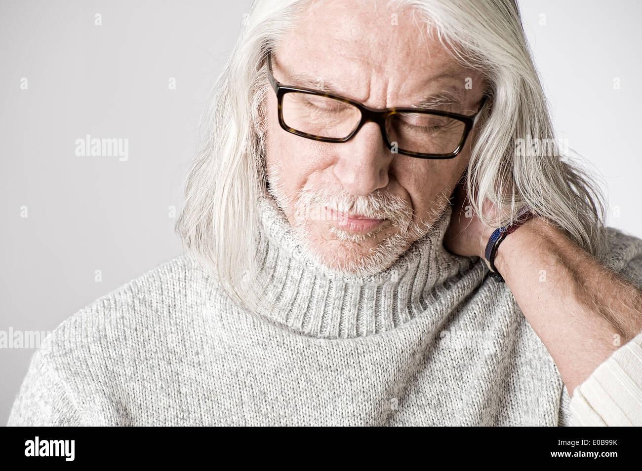Portrait of mature man, eyes closed, hand on head - Stock Image