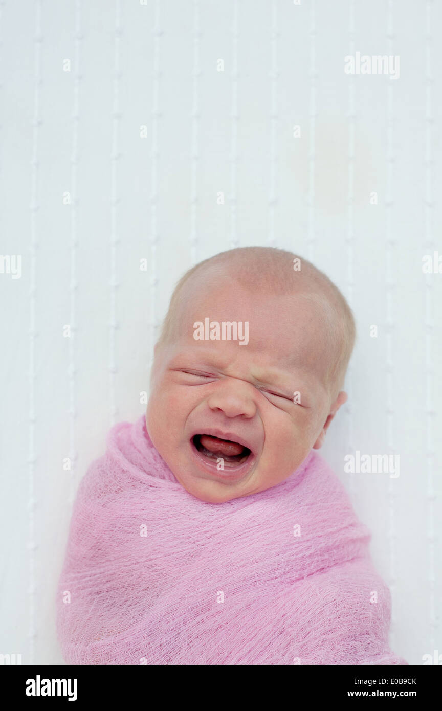 Baby crying, wrapped in blanket - Stock Image