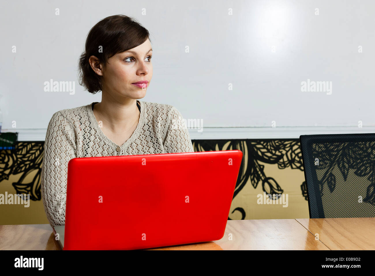 Young female designer daydreaming in design studio - Stock Image