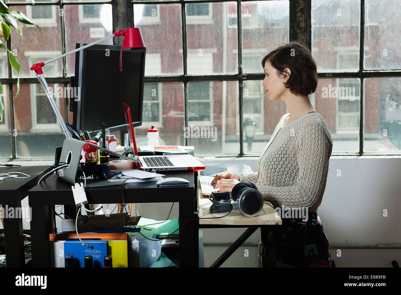 Young female designer using computer in design studio - Stock Image