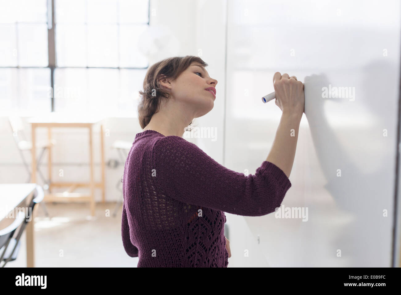 Young female designer drawing on whiteboard - Stock Image