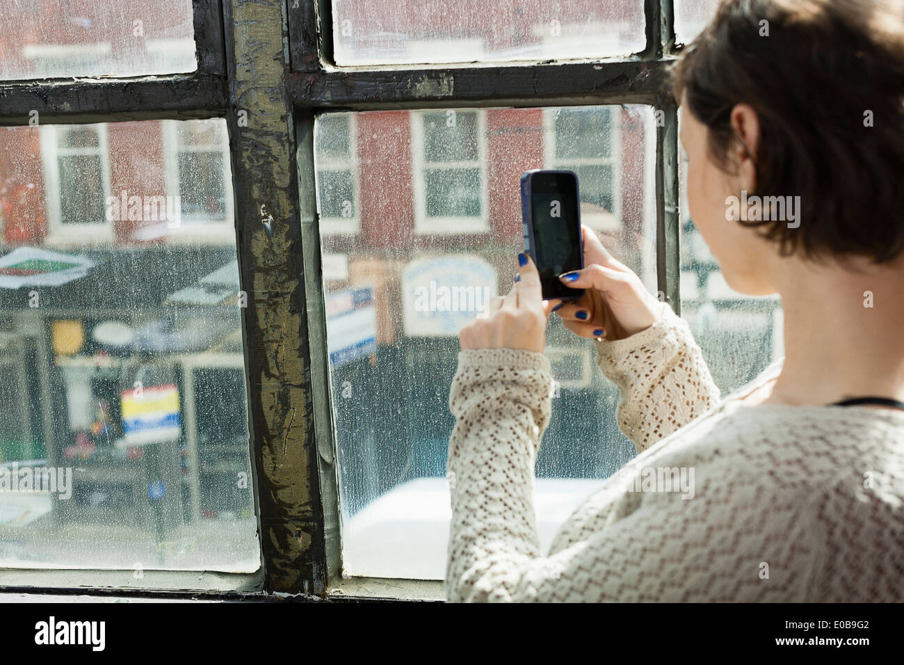 Young woman photographing street below from window - Stock Image